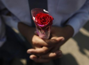 A student, holding a rose, takes part in a prayer for victims of the Taliban attack on the Army Public School in Peshawar, in Karachi